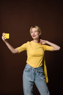 smiling blonde woman with bananas in string bag taking selfie by yellow smartphone isolated on brown