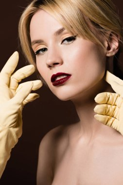 Human hands in yellow gloves and beautiful naked blonde girl looking at camera on brown stock vector