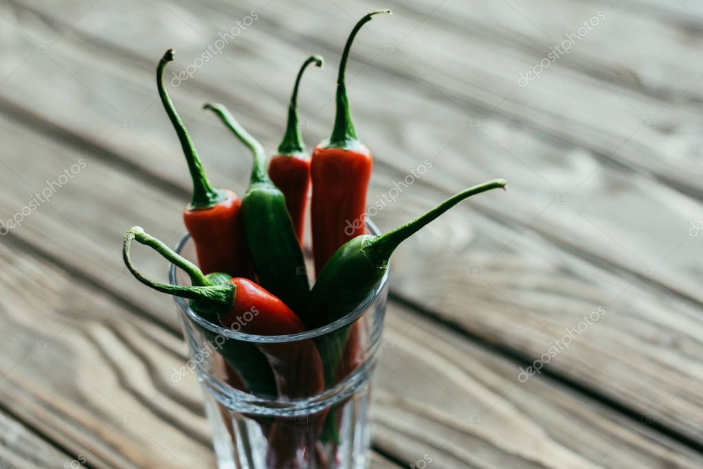 Bunch of peppers in glass on wooden table