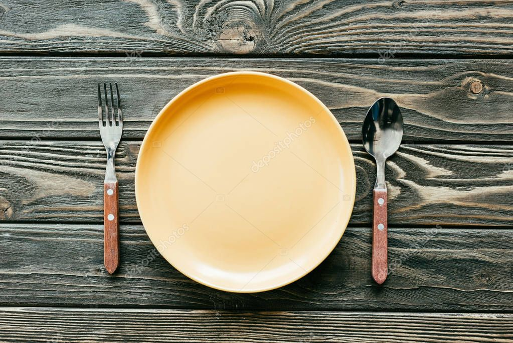 Plate with cutlery set on wooden table
