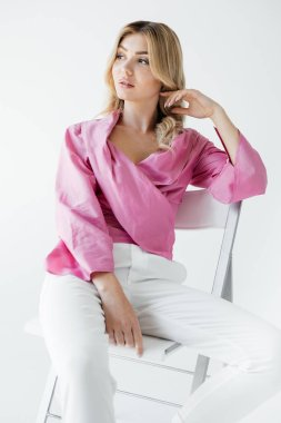 beautiful pensive blond woman in stylish clothing sitting on white chair on white backdrop