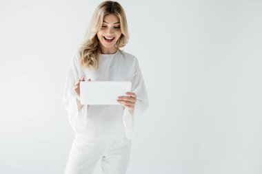 attractive cheerful woman in white clothing using tablet isolated on grey