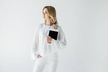 young attractive woman in white clothing with tablet posing isolated on grey
