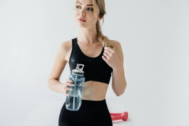 portrait of athletic woman in black sportswear with sportive water bottle on grey backdrop