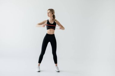 young athletic woman exercising with rubber tape isolated on grey