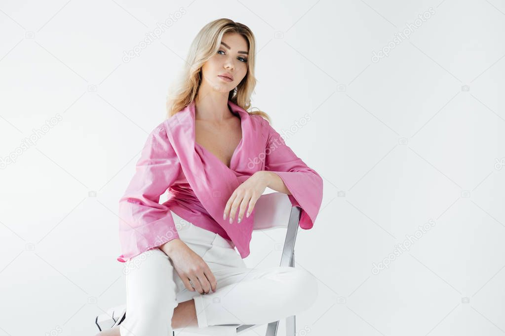 Beautiful young blond woman in stylish clothing sitting on white chair on white backdrop stock vector