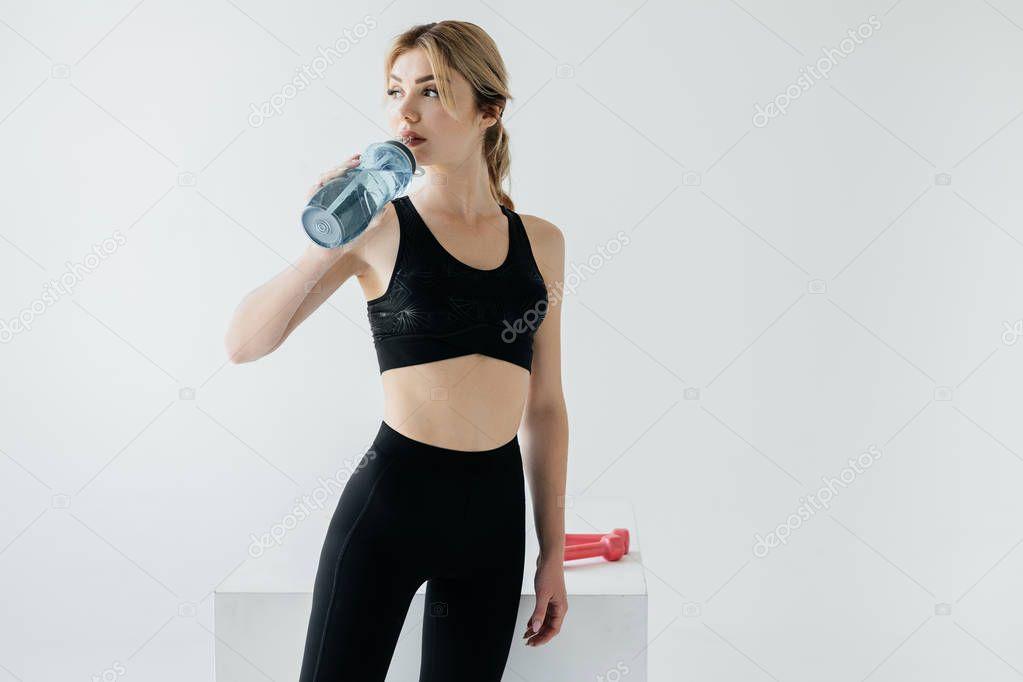 athletic woman in black sportswear drinking water from sportive bottle on grey backdrop