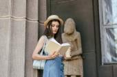 bella ragazza in cappello che tiene tazza di carta e libro di lettura vicino a colonna