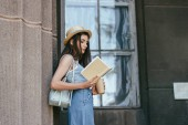 Fotografie side view of attractive girl in hat holding coffee to go and reading book near column