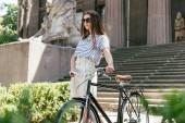 ragazza in occhiali da sole distoglie lo sguardo mentre levandosi in piedi con la bicicletta vicino bellissimo edificio con colonne e scale