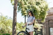 Fotografie low angle view of beautiful girl in sunglasses riding bicycle on street