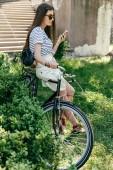 Fotografie krásná mladá žena v sluneční brýle sedí na kole a pomocí smartphonu