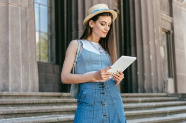 attractive smiling girl in hat using digital tablet while standing on stairs