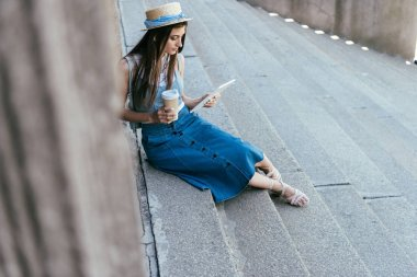 high angle view of young woman holding paper cup and using digital tablet while sitting on stairs