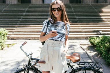 attractive girl using smartphone and smiling at camera while standing with bicycle on street