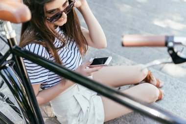 high angle view of girl in sunglasses sitting on stairs and using smartphone
