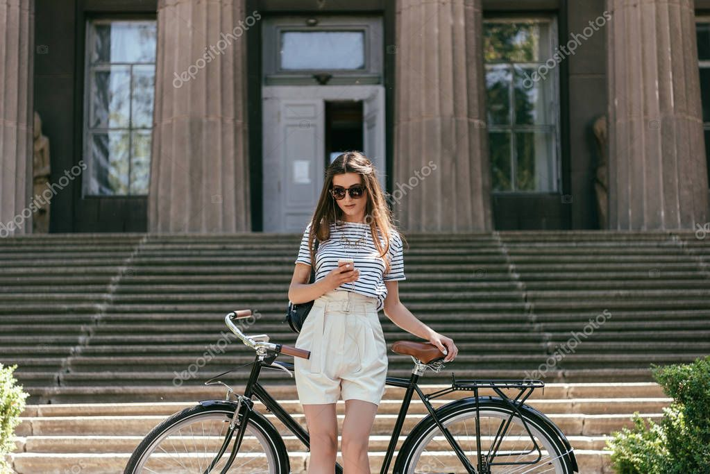 attractive girl in sunglasses using smartphone while standing with bike near beautiful building with columns and stairs