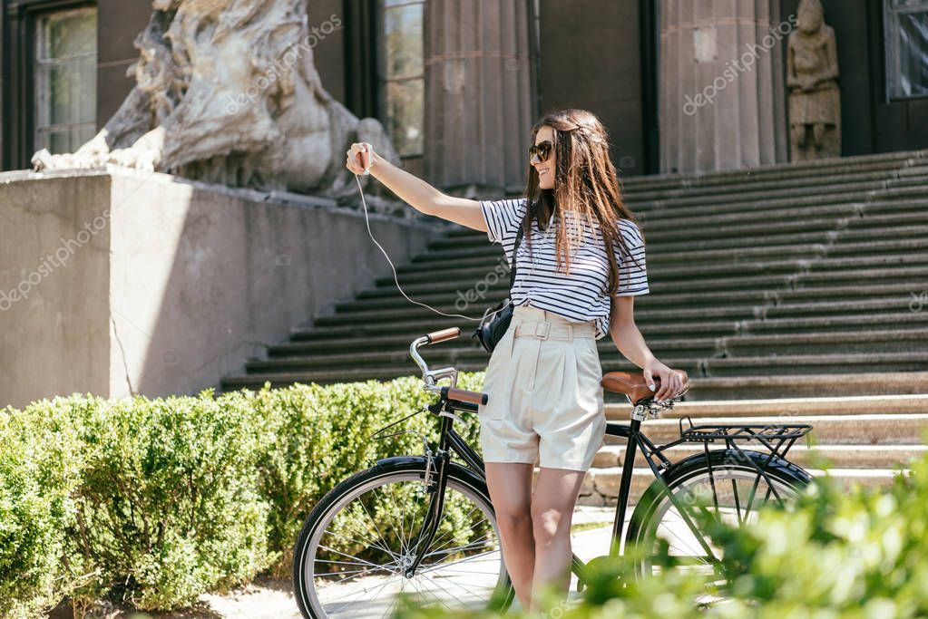 happy young oman in sunglasses taking selfie with smartphone while standing with bicycle near beautiful building with columns and stairs
