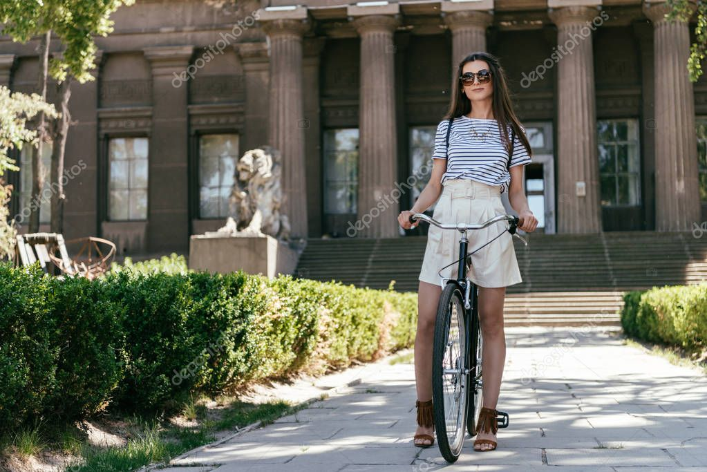 full length view of beautiful young woman in sunglasses riding bicycle on street