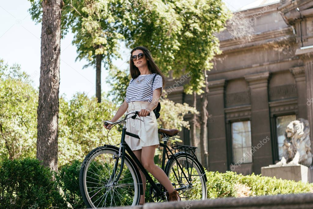 low angle view of beautiful young woman in sunglasses riding bicycle on street