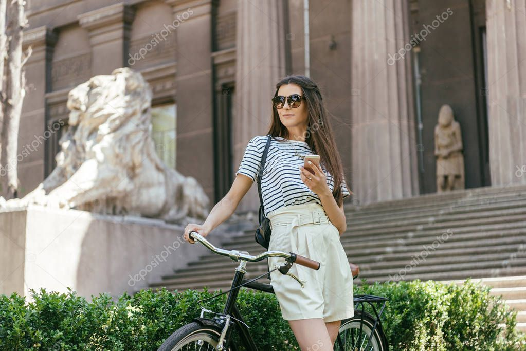 attractive girl with smartphone standing with bicycle near beautiful building with columns and stairs