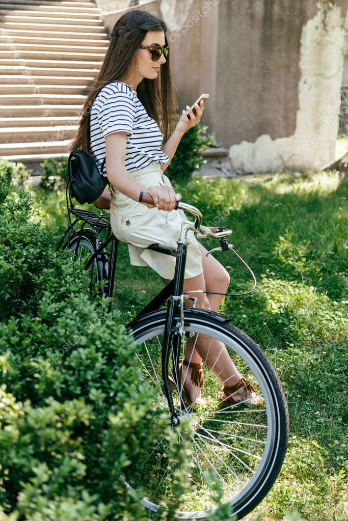 beautiful young woman in sunglasses sitting on bicycle and using smartphone