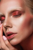 Photo close up of attractive girl with closed eyes and red makeup for fashion shoot