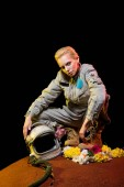 Photo stylish cosmonaut in spacesuit with flowers and helmet sitting on planet