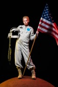 Photo beautiful astronaut in spacesuit holding helmet and american flag on red planet