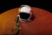 helma ze skafandru ležící na Rudé planetě v černém kosmu