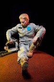 Photo beautiful astronaut in spacesuit with helmet sitting on planet