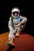 Fotografie young cosmonaut in spacesuit with helmet sitting on planet in space