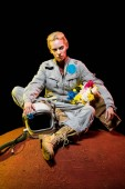 Photo fashionable cosmonaut in spacesuit with flowers in paper bag and helmet sitting on mars