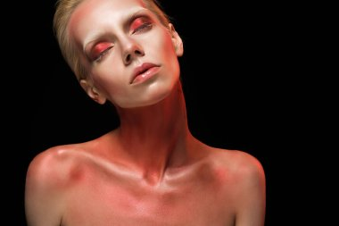 beautiful naked fashionable girl posing with red bodyart and closed eyes, isolated on black