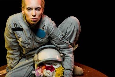 Cosmonaut in spacesuit with flowers in helmet sitting on planet stock vector