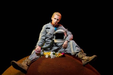 attractive spacewoman in spacesuit with flowers and helmet sitting on planet