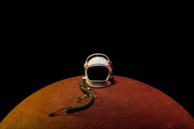 helmet from spacesuit lying on mars planet in black universe