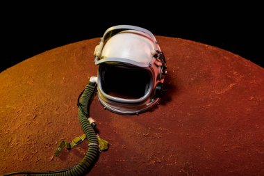 helmet from spacesuit lying on red planet in black cosmos