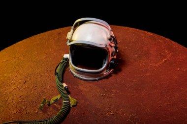 helmet from spacesuit lying on red planet in black cosmos