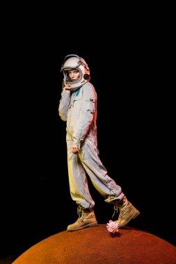 Cosmonaut in spacesuit and helmet standing on peony flower on planet stock vector