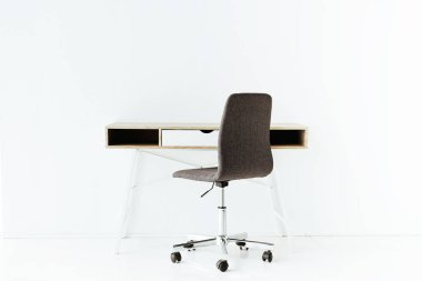 stylish empty work table and wheeled chair in front of white wall