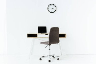 workplace with laptop in front of white wall at office
