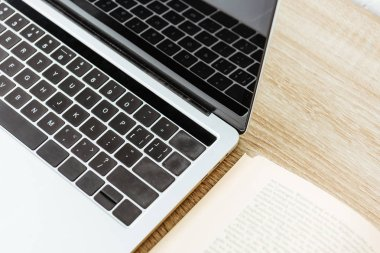 close-up shot of laptop with opened book on wooden surface