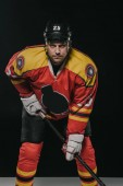 professional ice hockey player holding hockey stick and looking at camera on black