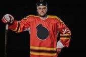 profesionální hráč ledního hokeje stál s rukou kolem pasu a při pohledu na fotoaparát izolované na černém pozadí
