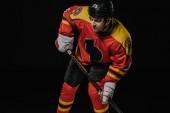 profesionální hokejista v držení hokejky a při pohledu od izolovaný na černém ochranné sportovní potřeby