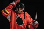 Fotografie professional hockey player adjusting helmet and holding hockey stick isolated on black