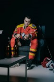 Fotografie young hockey player using remote controller and drinking beer while sitting in armchair and watching tv on black