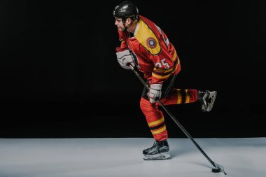 side view of young sportsman playing ice hockey on black
