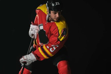 young hockey player in protective sportswear playing hockey isolated on black